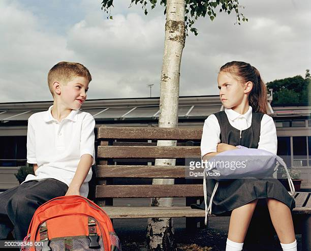 Boy (6-8) smiling at girl (6-8) sitting on bench