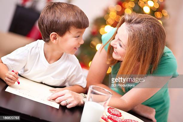 Boy Smiling at Mom While Writing Letter to Santa Claus