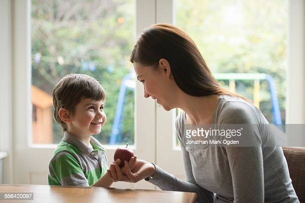 Boy smiling at mother as he hands her apple