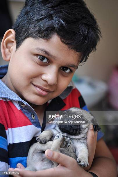 Boy Smiling Front of the Camera with a Pug Puppy while Holding the Baby Pug Tightly