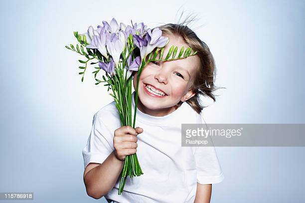 Boy smiling holding bunch of flowers