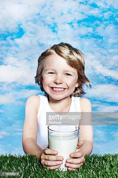 Boy smiling holding glass of milk