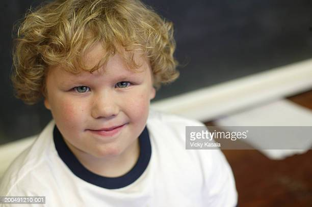Boy (6-8) smiling in classroom, portrait