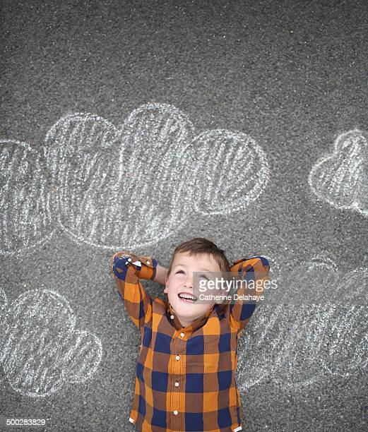 A boy smiling laying on a decorated road