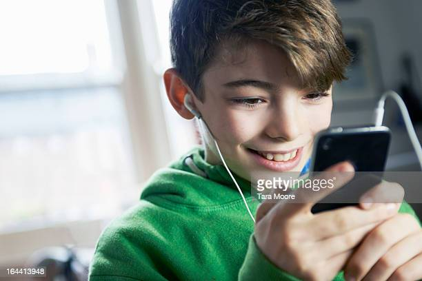 boy smiling looking at mobile with headphones