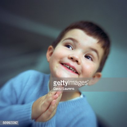 Boy smiling, looking to the side with hands together, portrait