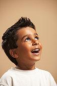 Boy (4-5) smiling, looking up, studio shot