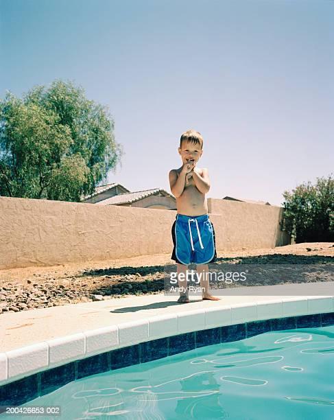 Boy (2-4) smiling near pool, portrait, close-up