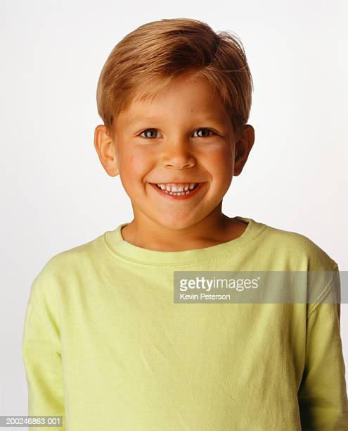 Boy (6-7) smiling, posing in studio, (Portrait)