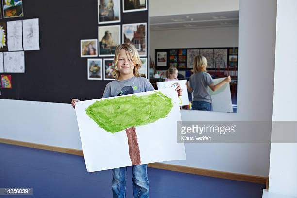 Boy smiling, showing his drawing of a tree