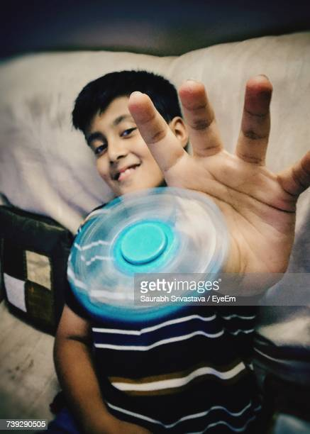 Boy Smiling While Playing With Fidget Spinner At Home