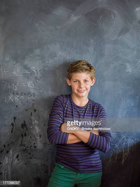 Boy smiling with his arms crossed in front of a blackboard in a classroom