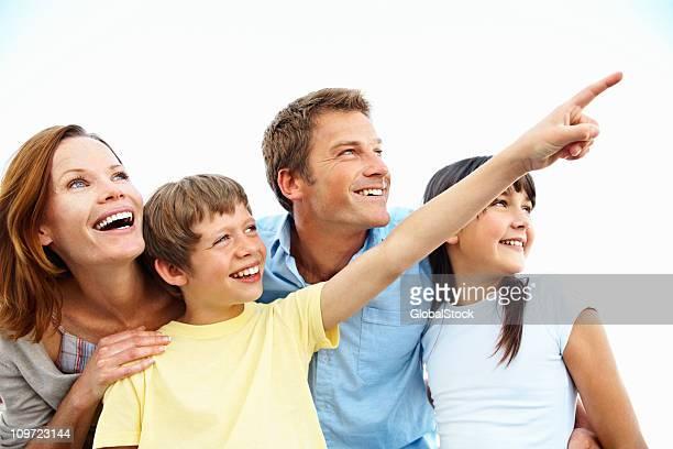Junge lächelnd mit seiner Familie und zeigt entfernt