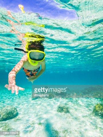 Boy snorkeling through Caribbean Sea