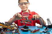 A younger boy is soldering a part onto a circuit board.  He is surrounded by miscellaneous tools and parts and is wearing safety glasses / goggles.
