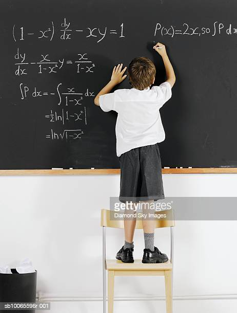 Boy (6-7) solving formula in classroom, rear view