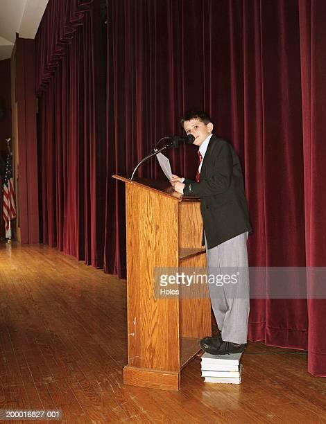 Boy (9-11) speaking at podium in auditorium, standing on books