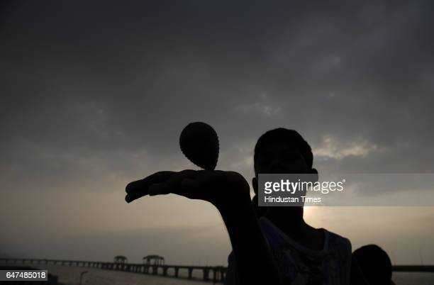 A boy spinning a top on a cloudy evening in Mumbai