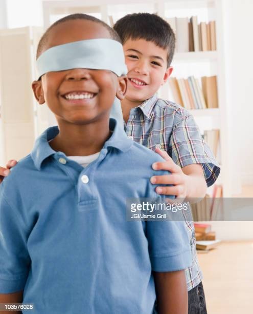 Boy spinning friend wearing blindfold