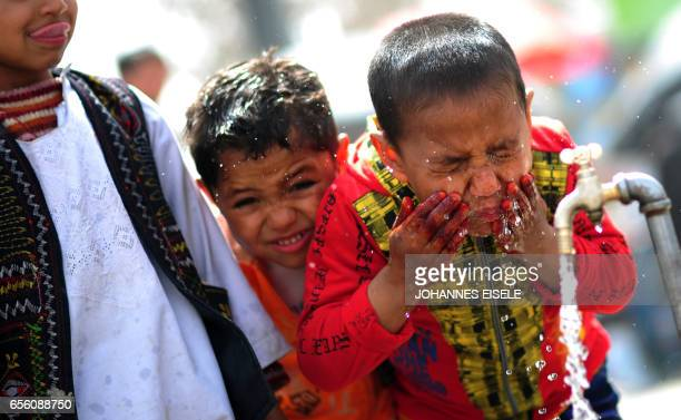 A boy splashes water on his face near the Hazrate Ali shrine in Mazari Sharif on March 23 2012 Children in Afghanistan suffer one of the highest...