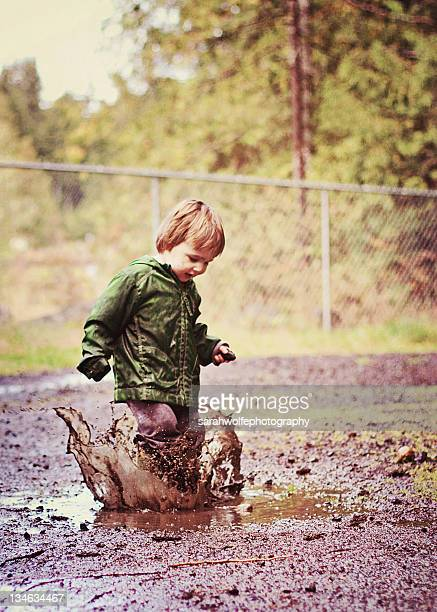 Boy splashing in mud puddle