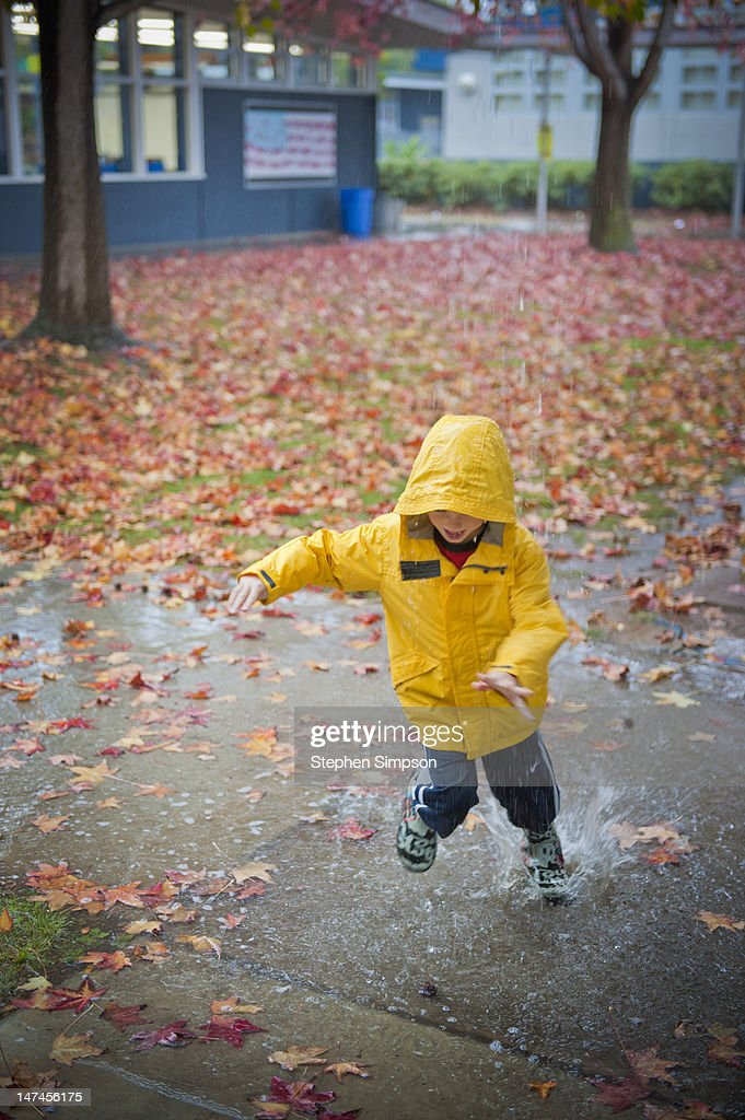 boy splashing in puddle on rainy Fall day : Stock Photo