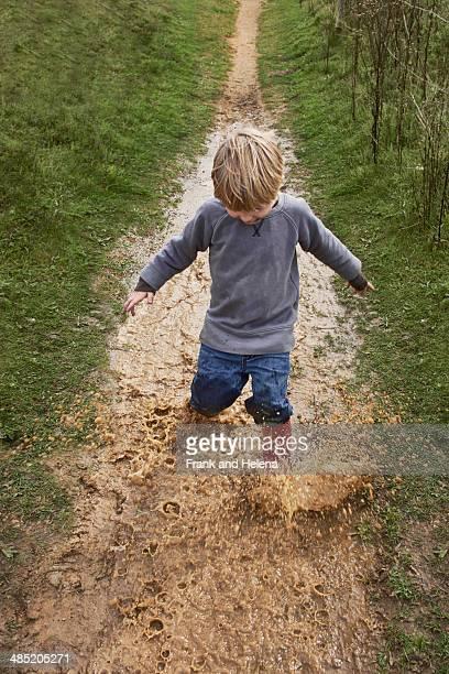 Boy splashing through muddy puddle