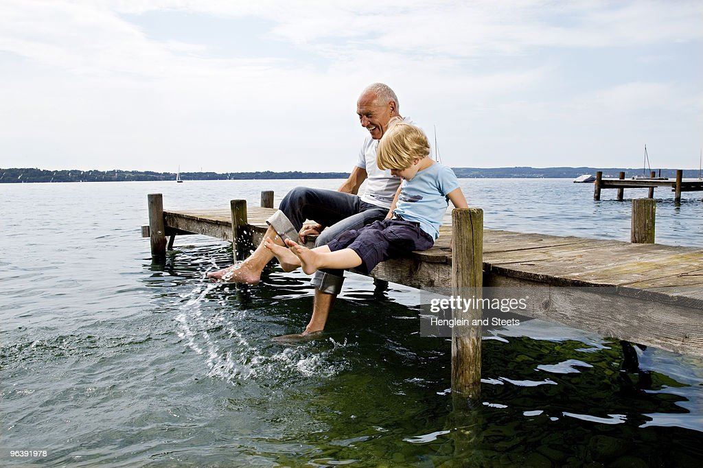 boy splashing with grandfather at lake : Stock Photo