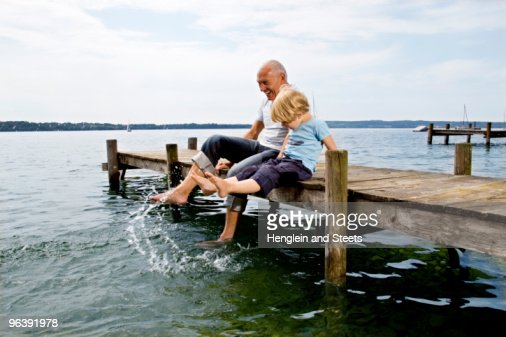 boy splashing with grandfather at lake : Stock Photo
