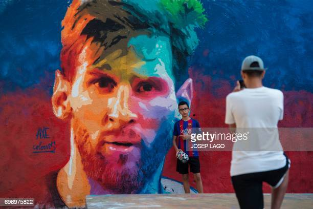 A boy sporting a Barcelona jersey poses for a photo beside a graffiti portraying Barcelona's Argentinian forward Lionel Messi on June 17 2017 in...