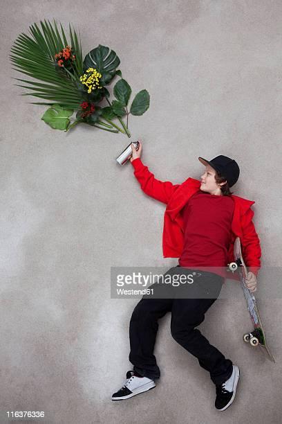 Boy spraying leaves from spray bottle