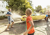 Boy spraying young man with hosepipe whilst washing vintage car