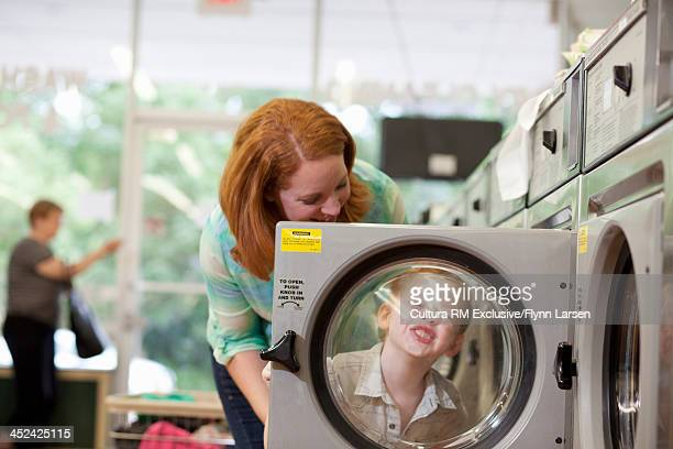 Boy squashing face against washing machine door, mother laughing