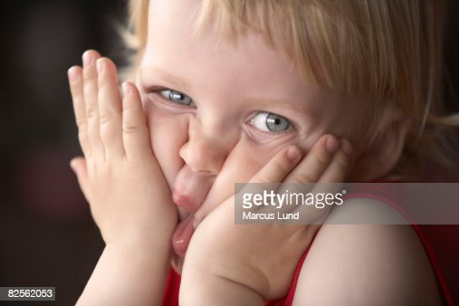 Boy squeezing face, looking at camera : Stock Photo