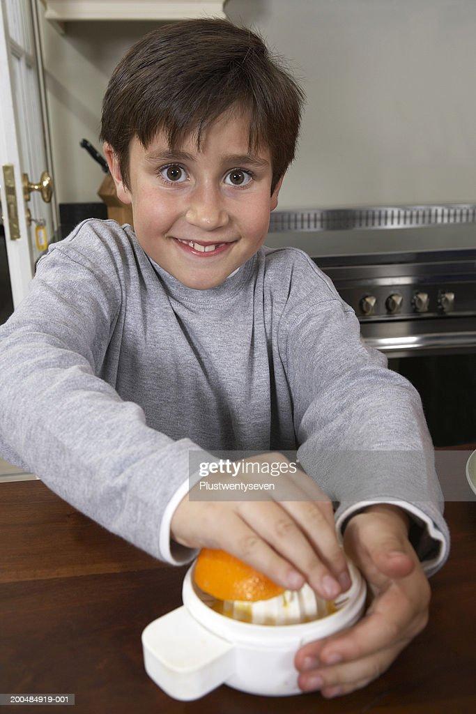 Boy (7-8)squeezing orange in kitchen, smiling, portrait : Stock Photo