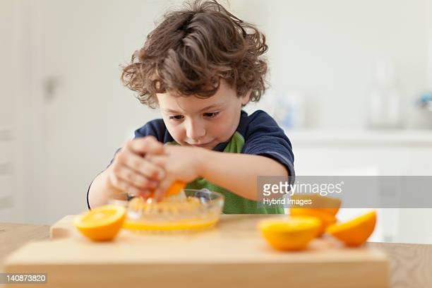 Boy squeezing oranges to make juice