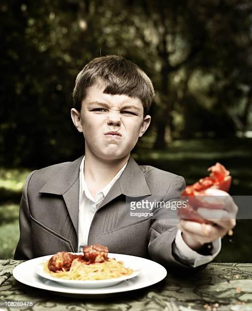Boy squeezing tomato