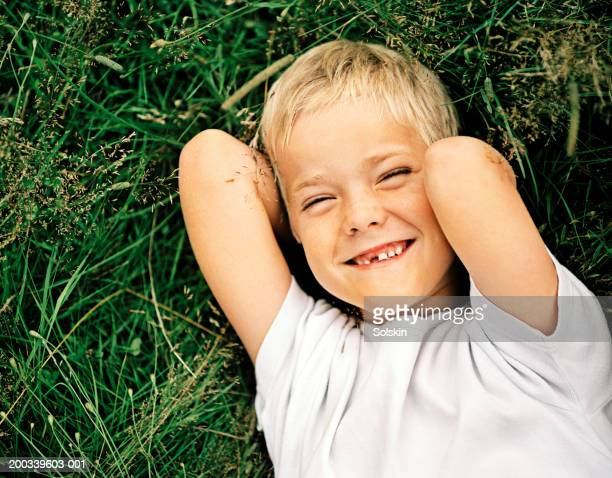 Boy (6-8) squinting with gap tooth lying on grass, portrait