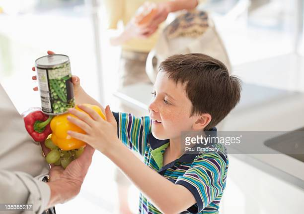 Boy stacking food into grandfather