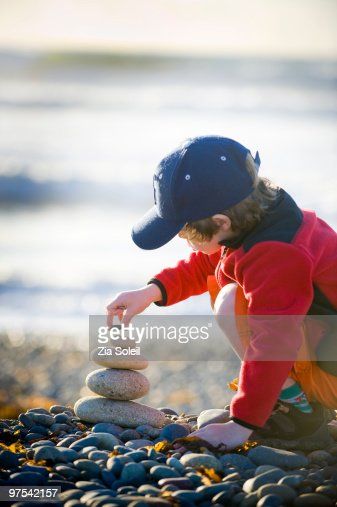 boy stacking rocks at the beach : Stock Photo