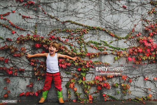 Boy (2-3) standing against a wall with ivy