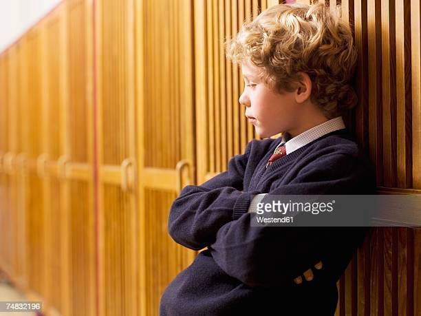Boy (4-7) standing and leaning on locker, side view, close-up