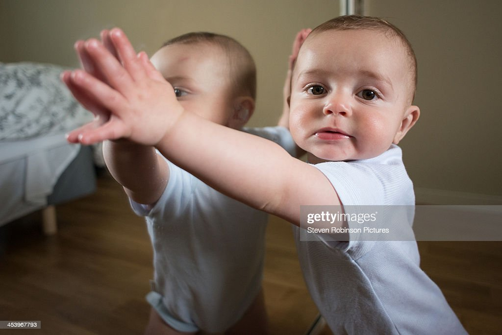 Boy standing at a mirror : Stock Photo