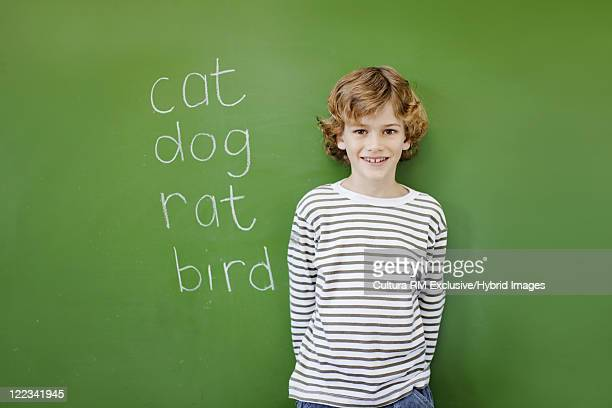 Boy standing at chalkboard in classroom