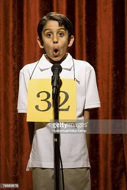 Boy standing at microphone speaking with number around neck