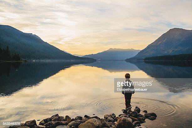 Boy (4-5) standing at waters edge looking at view