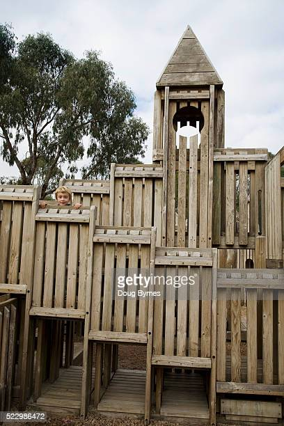 Boy Standing Behind Wall of Playground Fort