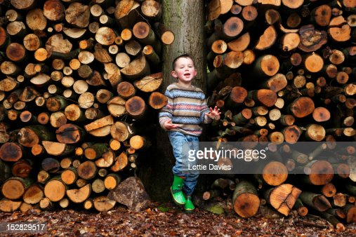 Boy standing by logs of wood