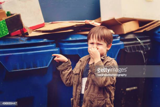Boy standing by stinky dumpsters