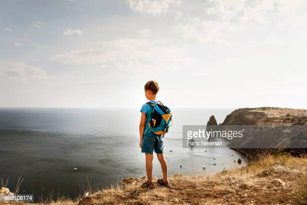 Boy standing by the cliff